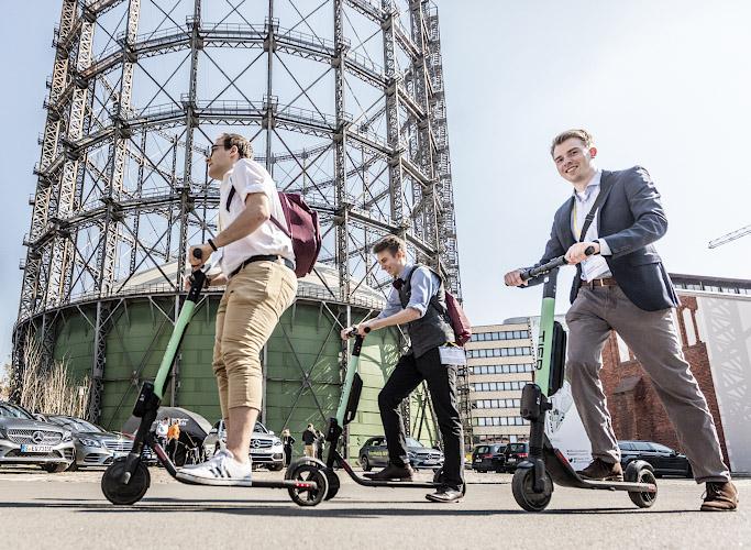 EUREF CAMPUS - Reallabor der Energiewende. Maenner testen E-Scooter von TIER auf Future Mobility Summit vor Gasometer. Berlin 2019