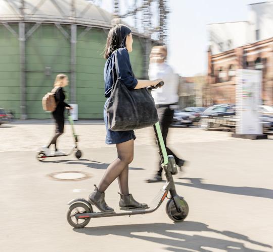 EUREF CAMPUS - Reallabor der Energiewende. Frau testet E-Scooter von TIER auf Future Mobility Summit vor Gasometer. Berlin 2019