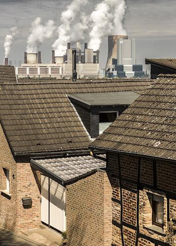 Dorf Oberaussem duckt sich vor RWE POWER AG Kraftwerk Niederaussem. Rheinisches Braunkohlerevier 2013