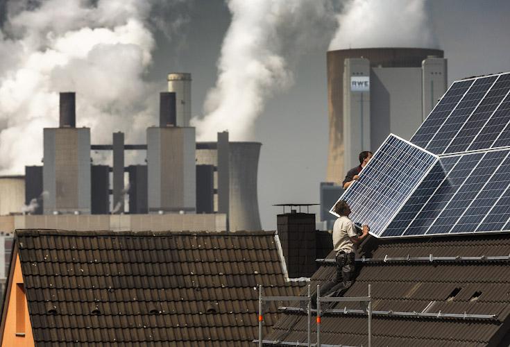 Solarteure in Aktion vor Kulisse RWE POWER AG Kraftwerk Niederaussem. Bergheim, Rheinisches Braunkohlerevier 2013